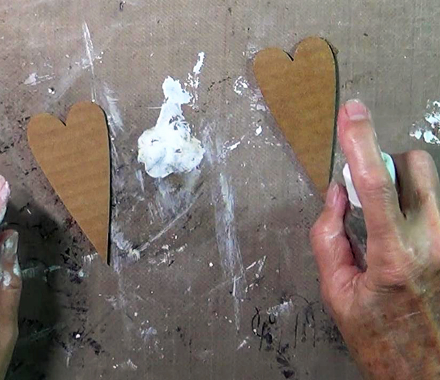 spritzing DIY scrapbook corrugated hearts with water
